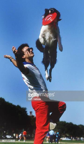 View as a border collie jumps above his owner to catch a frisbee during a contest Washington DC 1985