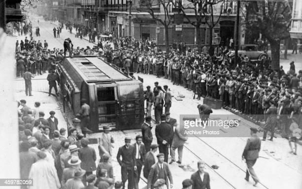 View as a rail car tipped over in the streets of San Sebastian, Spain. Circa 1940.