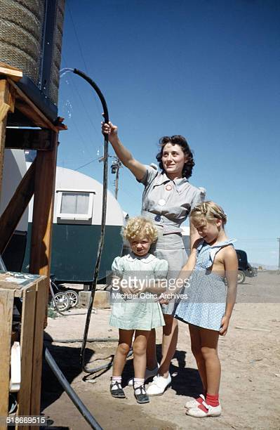 A view as a women gets water with his young girls at Tent City Nevada housing for workers and thier families at the Basic Magnesium Incorporated a...
