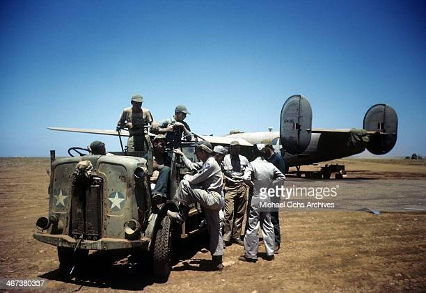 A view as crew members of the 98th Bombardment Group get a ride back to base as a B24 Liberator sits in the background at the US Air Force Base in...
