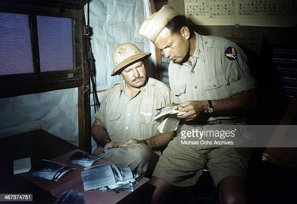A view as crew members of the 98th Bombardment Group inspect photographs at the US Air Force Base in Benghazi Libya