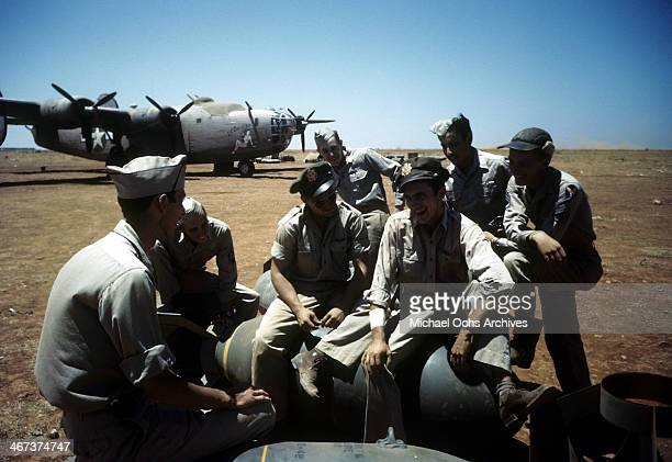 A view as crew members of the 98th Bombardment Group relax as a B24 Liberator sits in the background at the US Air Force Base in Benghazi Libya