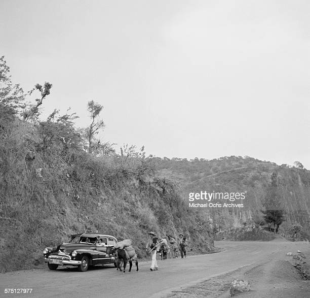 A view as man with his donkey pass a car on the road in Cuernavaca Mexico