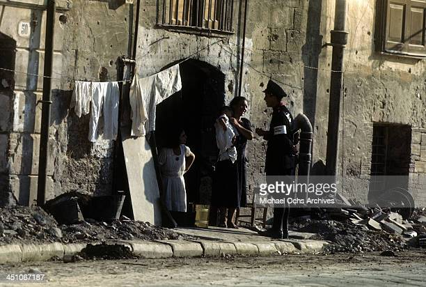 A view as Sicilian service member check on local family after the Allied forces on the campaign of the invasion of Sicily called Operation Husky...
