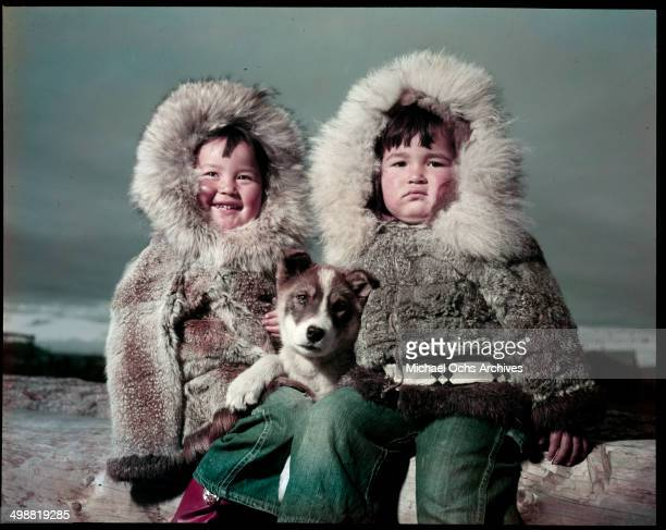 A view as the Inuit of Alaska as two young boys and dog pose by the beach in Alaska circa 1955