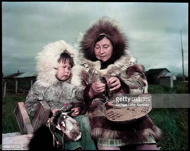 A view as the Inuit of Alaska women teaches a young girl how to sow in Alaska circa 1955