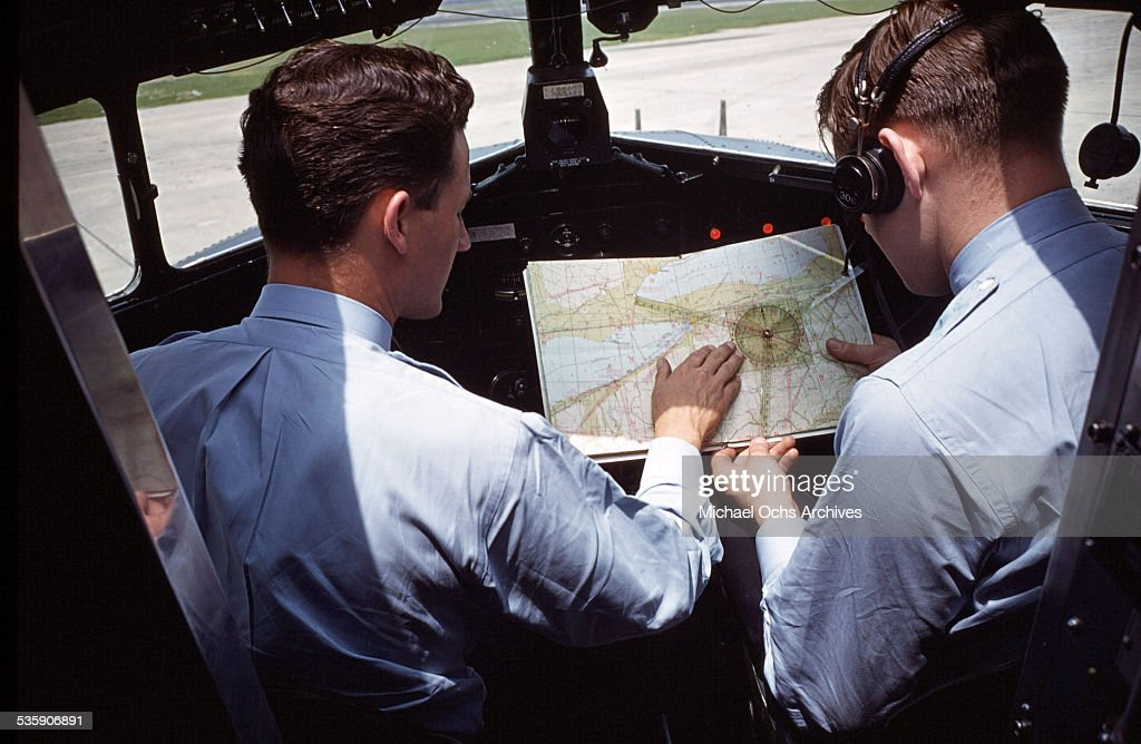A view as the pilots examine maps as they sit in the cockpit of a Convair Liner for American Airlines.