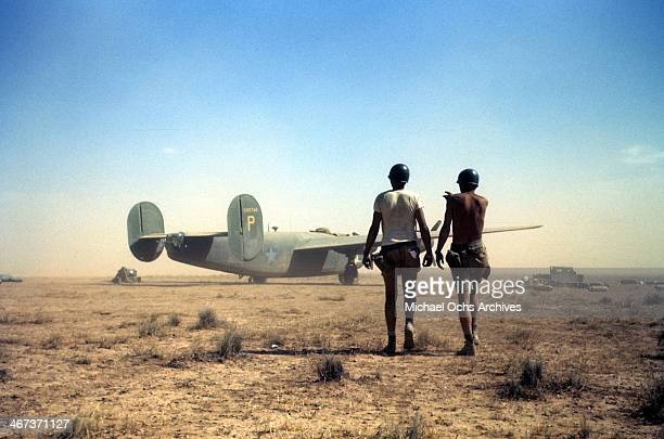 A view as two members of the 376th Bombardment Group walk in the desert as a B24 Liberator in the background at the US Air Force Base in Benghazi...