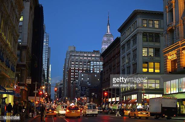 CONTENT] View at night of 6th Avenue Manhattan and Empire State Building City urban night avenue street car cars busy dusk skyline cityscape...