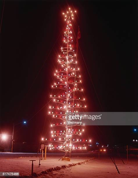 View at night of a 45-foot high Christmas tree constructed of sections of metal pipe by airmen at the U.S. Air Force base, 690 miles north of the...