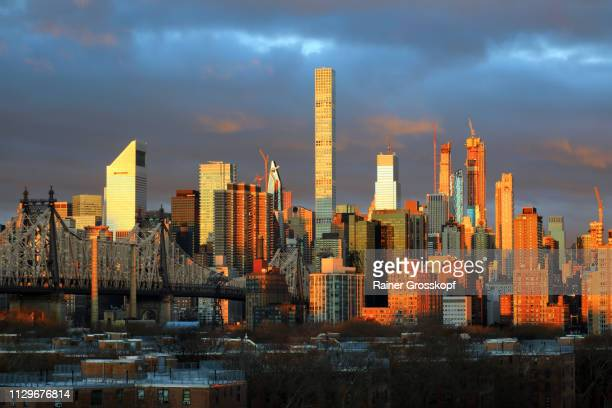 view at queensboro bridge and skyline of midtown manhattan at a glowing sunrise - rainer grosskopf fotografías e imágenes de stock
