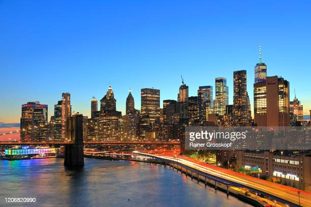 view at the skayline of downtown manhattan at dusk with light trails of the moving rush hour traffic - rainer grosskopf stock pictures, royalty-free photos & images