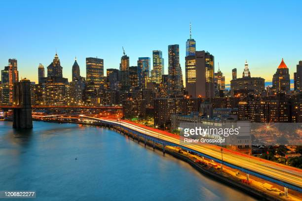 view at the skyline of downtown manhattan at dusk with light trails of the moving rush hour traffic - rainer grosskopf stock pictures, royalty-free photos & images