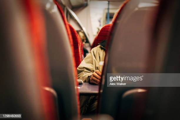 view between seats on train of person holding coffee cup - table stock pictures, royalty-free photos & images