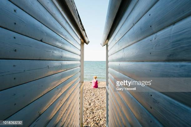 view between two beach huts to the beach - finding stock photos and pictures