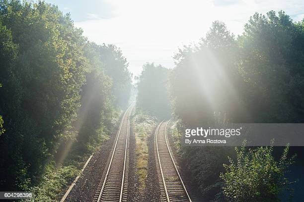 View brom bridge down to railroad tracks with rays of morning sun