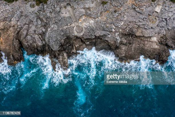 a view directly above a steep rocky shoreline coming out of the sea - water's edge stock pictures, royalty-free photos & images