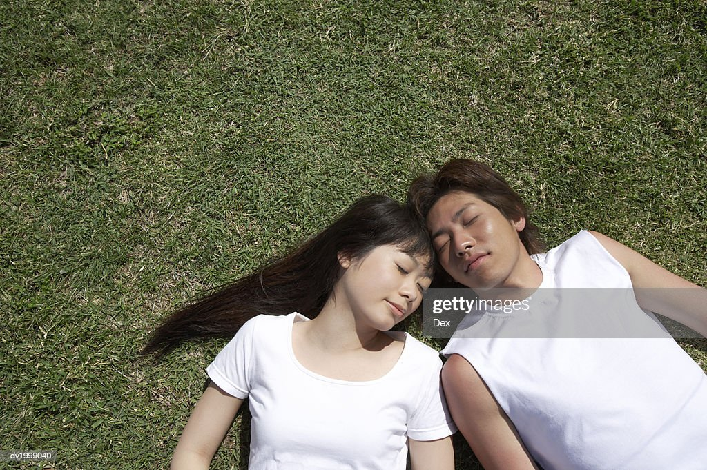 View Directly Above of a Young Couple Sleeping on the Grass Side by Side : Stock Photo