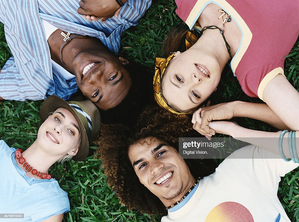 View Directly Above of Four Young Man and Women Lying in a Circle on the Grass, Smiling : Stock Photo