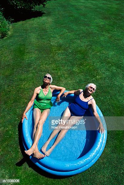 view directly above of two senior women lying in a paddling pool, wearing swimsuits - women sunbathing stock photos and pictures