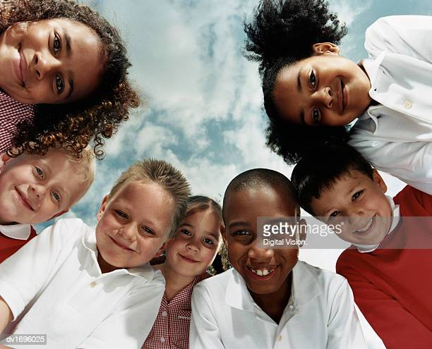 view directly below of seven primary school children huddled together looking at the camera - school children stock pictures, royalty-free photos & images