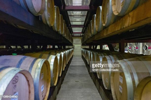 View down a dark row of traditional wooden wine barrels used for aging wines on racks at a wine production facility in Sonoma County Healdsburg...