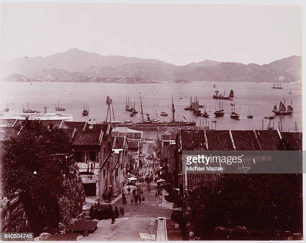 View down a street of Hong Kong looking towards Victoria Harbor ca 1880s Several sailboats of various sizes are anchored in the harbor
