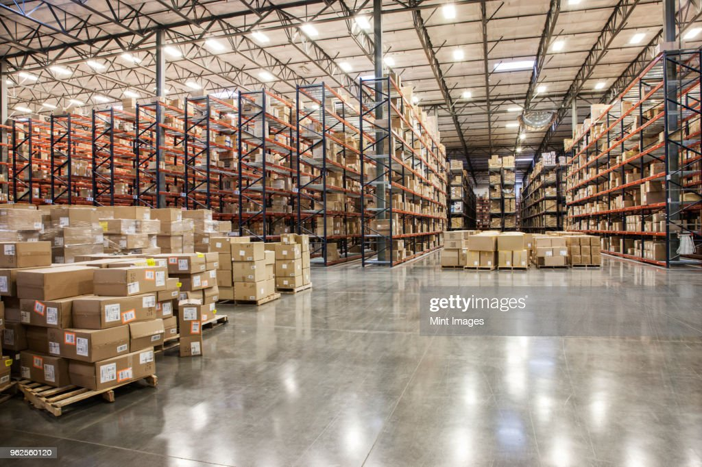 View down aisles of racks holding cardboard boxes of product on pallets in a large distribution warehouse : Stock Photo