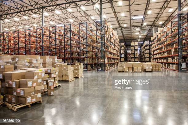 View down aisles of racks holding cardboard boxes of product on pallets in a large distribution warehouse