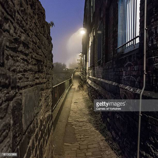 View down an old, dark and gloomy cobbled alleyway next to the River Sheaf and Sheaf Bank Business Park in Heeley, Sheffield, UK.