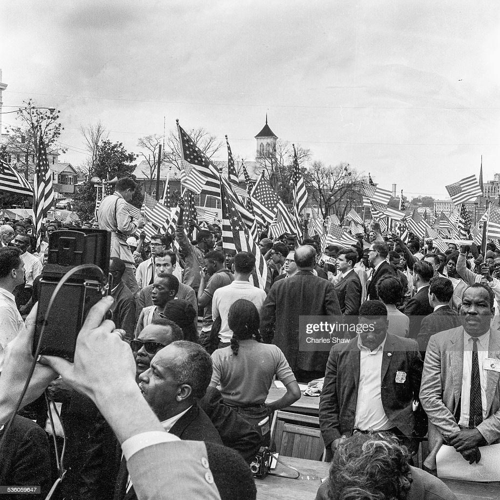 View down Dexter Avenue (seen from a podium in front of the Alabama State Capitol) across press tables and a sea of marchers and American flags at the end of the Selma to Montgomery March, Montgomery, Alabama, March 25, 1965. The Dexter Avenue Church, where Martin Luther King Jr was pastor from 1954-1960, is at center behind the flags.