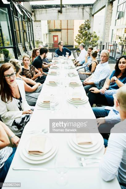 View down long table of group of friends seated for celebration meal on outdoor patio