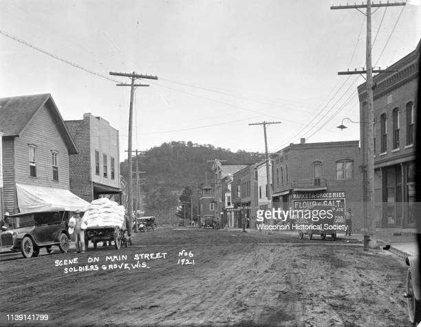 View down Main Street with steep treecovered hill in the far background Soldiers Grove Wisconsin 1921 On the left a man is holding flour sacks and...