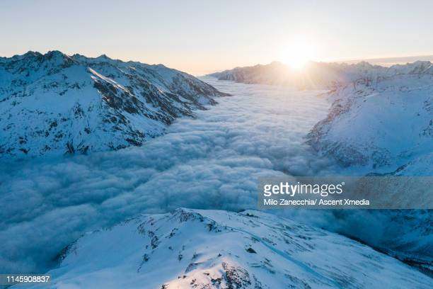 view down mountain valley as clouds lift in the morning sun - russia stock pictures, royalty-free photos & images