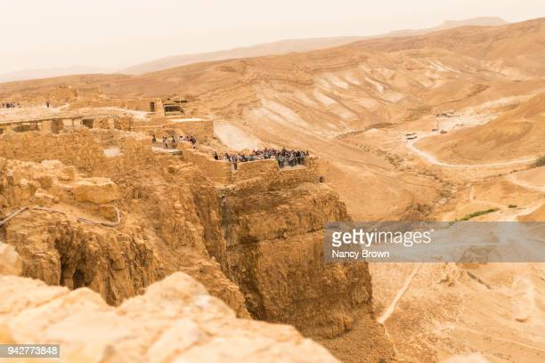 View down on Ruins of Masada with Tourist near Jerusalem in Israel.