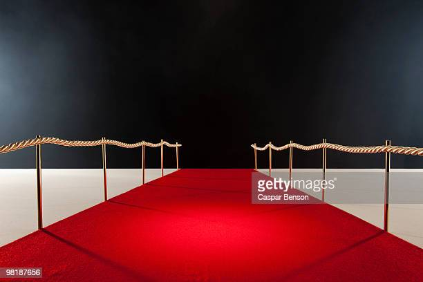 view down red carpet with rope barriers - gala stock-fotos und bilder