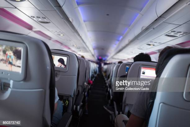 View down the aisle of the coach class section of a Virgin America aircraft in flight with inflight entertainment consoles on seat backs visible...