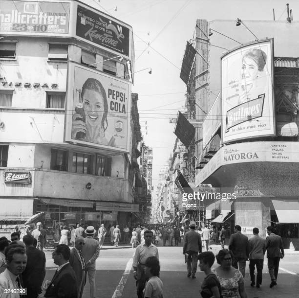 View down the busy Calle Florida, a pedestrian shopping mall, Buenos Aires, Argentina, 1960s. Visible business include the Etam clothing store at...