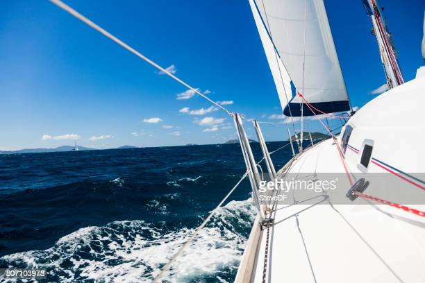 View down the side deck of a sailboat under sail in the Caribbean