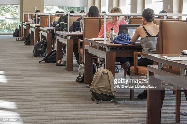 View down the sunny aisle of the Albert Hutzler Reading Room, a two-story silent reading room in the Brody Learning Commons of Johns Hopkins...