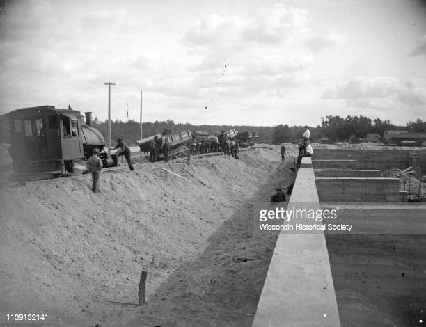 View down wall towards a construction site Black River Falls Wisconsin 1911 On the right arec men by a railway track with sand haulers and a brick...