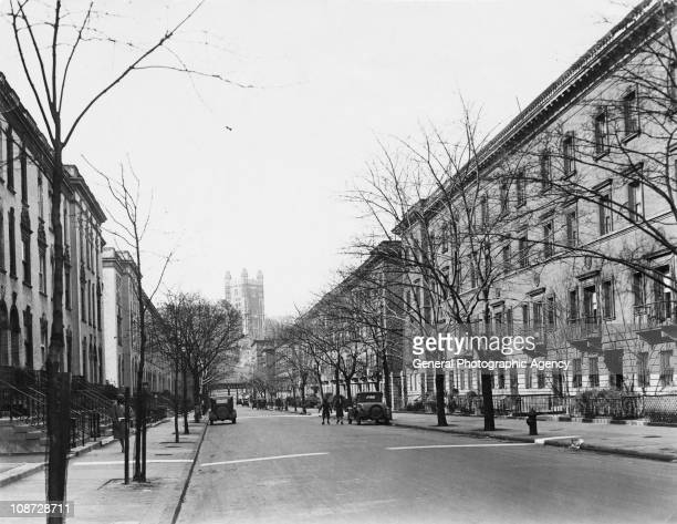 A view down a street in Harlem New York City with the tower of the College of the City of New York in the background circa 1930