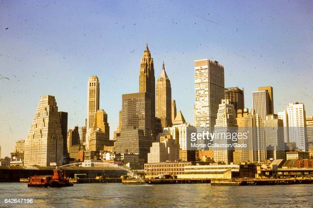 View facing west of morning sun shining on skyscrapers in lower Manhattan New York City August 1966 A fire boat in the East River sprays water toward...