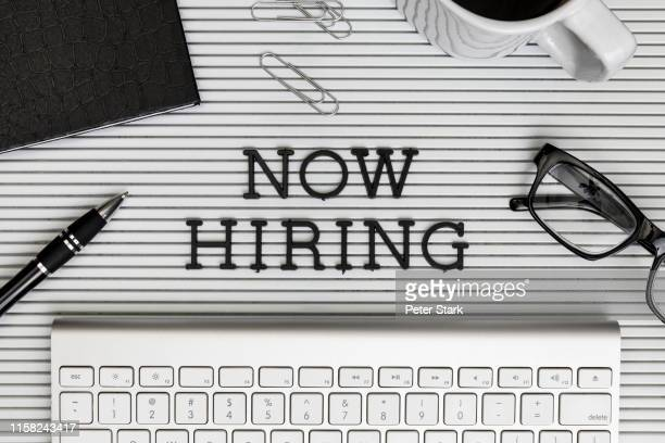 "view form above ""now hiring"" text on desk above computer keyboard - recruitment stock pictures, royalty-free photos & images"