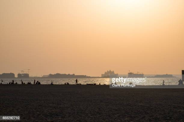 view from a dubai beach across to the palm as the sun is beginning to set. - claire plumridge stock pictures, royalty-free photos & images