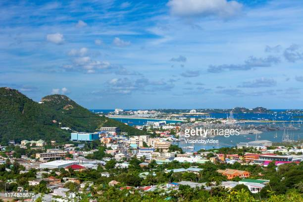 uitzicht vanaf een heuveltop van st maartin, nederlandse antillen met uitzicht op de stad en de marina beneden en de luchthaven (sxm) in de verte - sint maarten caraïbisch eiland stockfoto's en -beelden