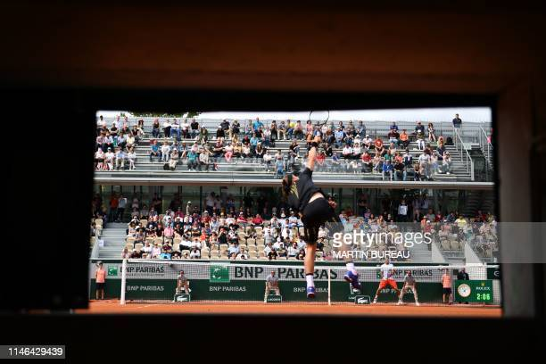 View from a photographer position of Slovakia's Jozef Kovalik serving the ball to Switzerland's Stanislas Wawrinka during their men's singles first...