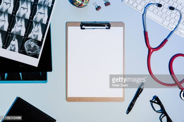 view from above blank paper on clipboard next to x-rays and stethoscope - clipboard stock pictures, royalty-free photos & images