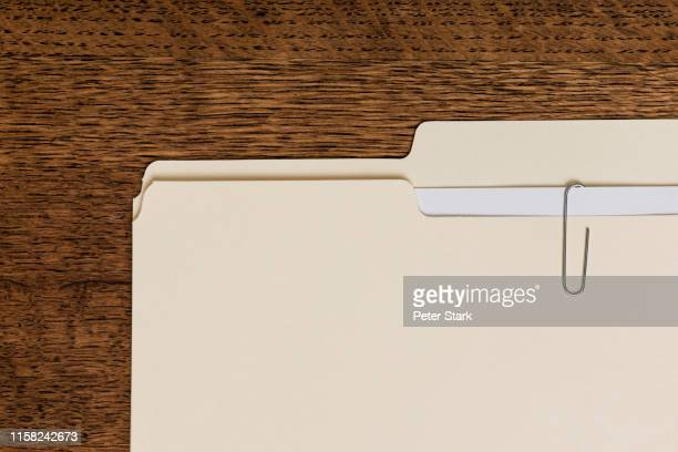 view from above manila folder and paperclip on wooden surface - akte stock-fotos und bilder