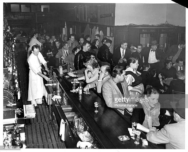 A view from above of a busy bartender pouring drinks for a thirsty and lively crowd inside Goody's Bar in Greenwich Village New York 1955